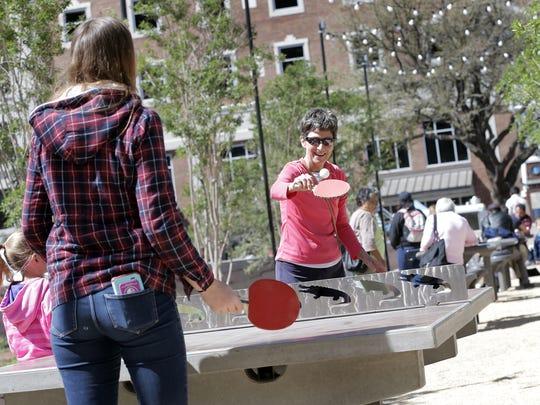 Families play pingpong Saturday during San Jacinto Plaza's grand reopening.