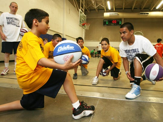Instructor Joey Hidalgo, right, leads participants, including James Shaheen, left, in a drill during the 2011 Basketball in the Barrio on Friday at the Armijo gym.