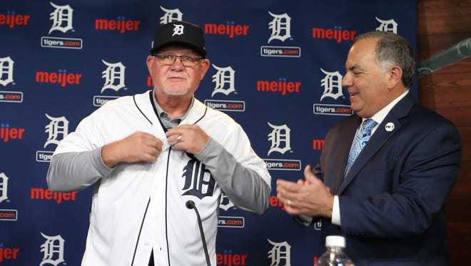 New manager Ron Gardenhire, left, puts on his Tigers jersey as general manager Al Avila applauds at the introductory press conference on Friday.