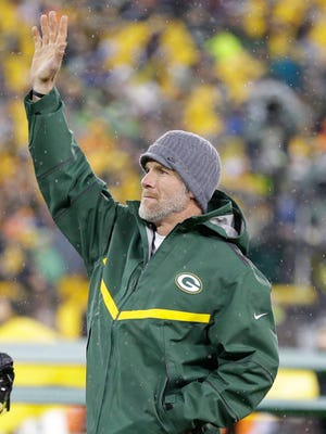 Brett Favre waves to the crowd as he is introduced at halftime for his number retirement ceremony at Lambeau Field November 26, 2015.