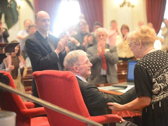 Vermont House Clerk Don Milne, seated, receives a sustained