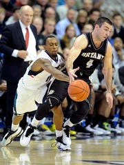 Bryant's Shane McLaughlin, right, dribbles by UConn's