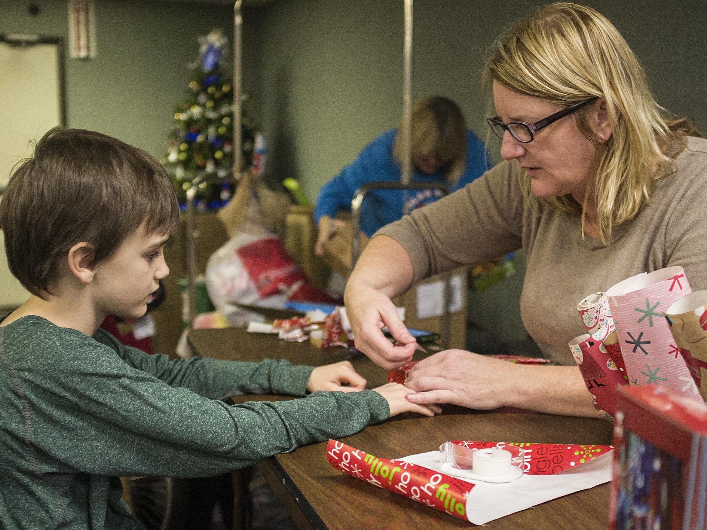 Gavin Dewey, 8, helps his mom Tina wrap presents for homeless children living in the Magnuson Hotel in Lansing Saturday, Dec. 5.