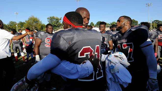 Lane College head coach Derrick Burroughs hugs defensive back Justin Hill (21) after the Dragons defeated Benedict College 19-18 at Lane Field in Jackson on Oct. 8, 2016.