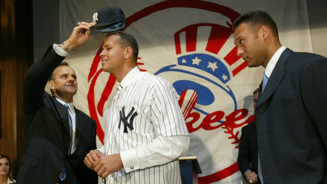 Yankees manager Joe Torre puts a cap on the newest member of the team, Alex Rodriguez, as teammate Derek Jeter looks on at a news conference at Yankee Stadium on Feb. 17, 2004.