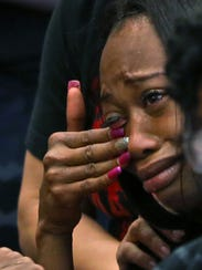 Erica Bailey, daughter of Aaron Bailey, tears up as