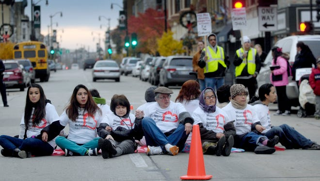 People hold hands and block a street during an immigration reform demonstration Nov. 8 outside Rep. Paul Ryan's office in Racine, Wis.