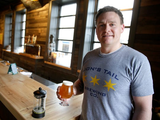 Lion's Tail Brewing Co. owner Alex Wenzel holds one