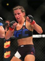 Jessica Eye (blue gloves) fights against Miesha Tate