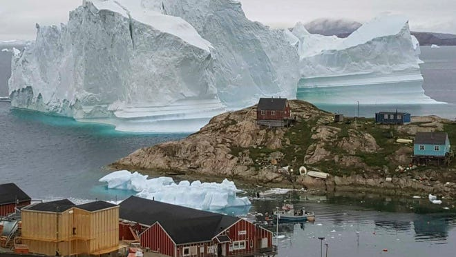 A view of an Iceberg July 12, 2018, near the village Innaarsuit, on the northwestern Greenlandic coast. Scientists have watched an iceberg four miles long break off from a glacier. The iceberg is allegedly grounded on the sea floor.