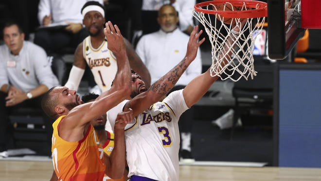 Los Angeles Lakers forward Anthony Davis (3) is fouled by Utah Jazz center Rudy Gobert (27) during the first half of a NBA game at The Arena at the ESPN Wide World of Sports Complex on Monday in Lake Buena Vista, Fla.