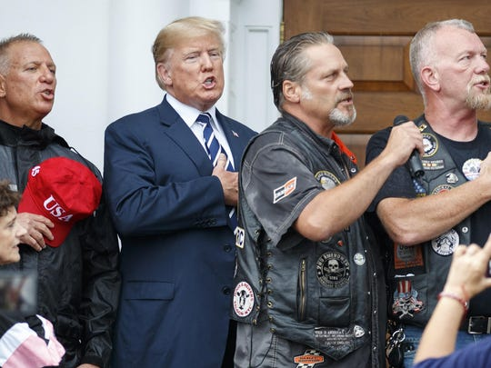 President Donald Trump stands with Bikers for Trump members as they say the Pledge of Allegiance on Saturday at Trump National Golf Club in Bedminster, New Jersey.