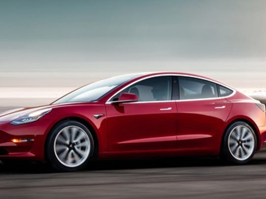 A red Tesla Model 3, an upscale compact sports sedan.