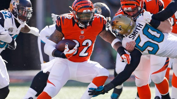 Bengals running back Jeremy Hill hits the hole for a gain against the Jaguars on Sunday.