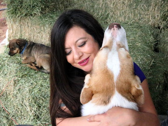 State Rep. Mary Gonzalez cuddles with Goat, one of her six dogs on her family's farm outside Clint, TX.