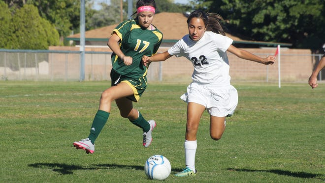 Eighth grade Lady Cat Nicole Lopez (22) wins a free ball over a Mayfield player during Tuesday's 4-1 loss to the Trojans in District 3-6A soccer. The Deming High varsity will host Onate at 10 a.m. Saturday at the DHS Soccer Field.