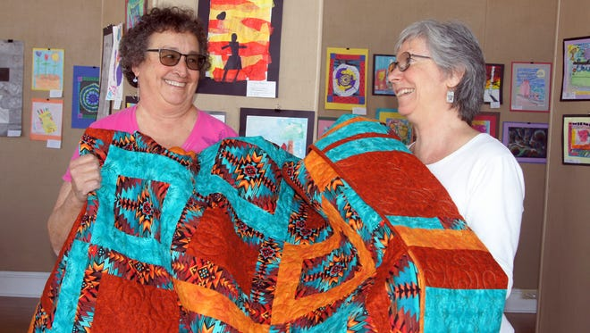 """Quilting B's members, Marilyn Goble, left, and Janet St. Cyr, hold up the """"Southwest Sunset"""" quilt that will be raffled off during the club's Trunk Show at 1 p.m. on Saturday at the Deming-Luna-Mimbres Museum. The club is hosting its third annual Quilt Show from 9 a.m. to 4 p.m., Thursday Friday and Saturday in the Transportation Room of the museum."""