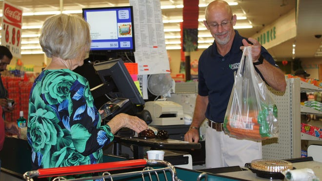 Peppers Supermarket General Manager Mark Schultze gets behind the counter to help check out during a Wednesday sale day.