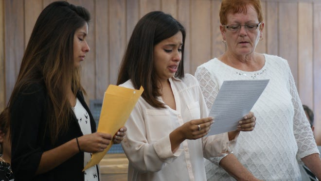 With Sandusky County Vicitm's Advocate Deb Wells, far right, Alexandra, left, and Samantha Rojas, right, read statements to Mauricio Valois-Perez, who shot and killed their sister Gabrielle Rojas last December.