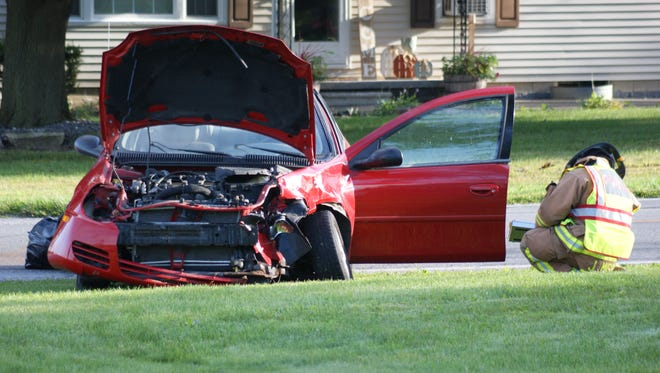 A red Dodge Neon is damaged when the driver failed to yield at a stop sign, crashing into a maroon Dodge Avenger.