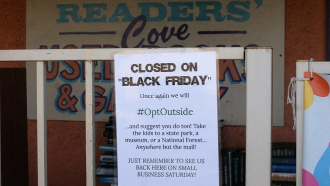 A sign on the gate of Reader's Cove Used Books and Gallery on Copper Street shoos customers outside for Black Friday.