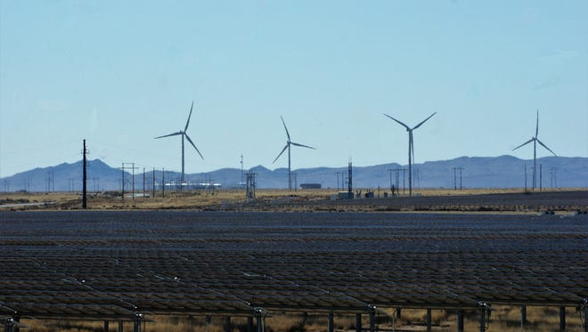 Turbines belonging to the Macho Springs Wind Farm are seen behind an array of solar panels near the old town of Nutt on NM state highway 26 in January 2018.