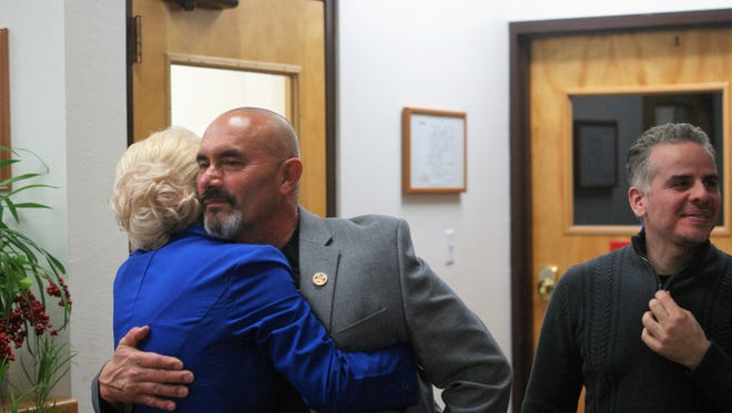 Mayor Benny Jasso, center, hugs his wife, Natasha Jasso, upon hearing he had won a second term. At right is Councilor Victor Cruz.