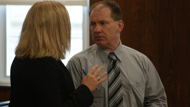 Daniel Myers consults with co-counsel Jane Roman of Toledo after his case was continued during a Wednesday pretrial.