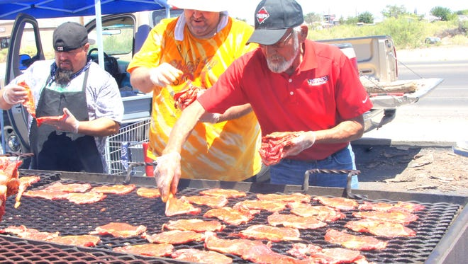 Manny Martinez, right, won't say how many years he's been grilling for Peppers Supermarket and he hasn't lost his touch for the Hereford Beef rib-eye steaks.