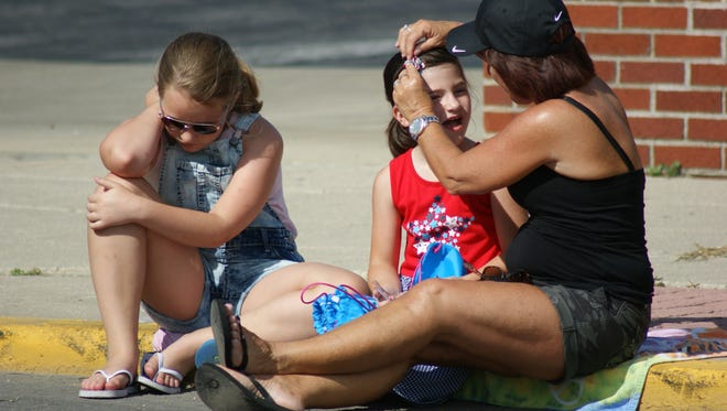 Dana Miller puts a hair clip in Marlee Brust's hair while Sabrina Brust waits for the Fourth of July parade to start Wednesday in Fremont.