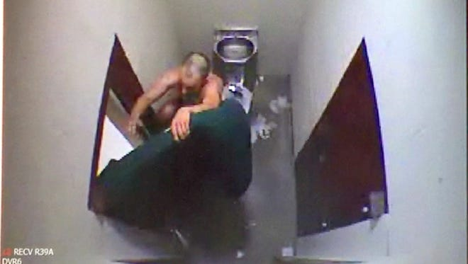 Escape suspect Marcus Bramlett climbs a door Monday inside a bathroom at the Tippecanoe County Jail before he hung from the ceiling and fell to the floor. The video was released Wednesday by Tippecanoe County Sheriff Barry Richard.