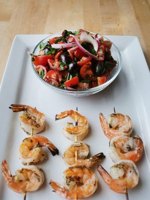 In this Grilled Shrimp with Bread Vegetable Salad recipe, the shrimp is brushed with a mix of olive oil, plenty of fresh lemon juice, garlic, salt and pepper. We grilled the shrimp, but you can pan-sauté it, broil or bake it.