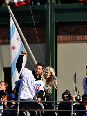 Chicago Cubs baseball player Ben Zobrist pumps his fist while wife Julianna looks on outside Wrigley Field during a parade honoring the World Series champions Friday, Nov. 4, 2016, in Chicago. (AP Photo/Paul Beaty)