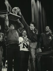 Milwaukee North's Greg Melton hoists the school's WIAA championship trophy during a school assembly in 1980 as teammate Gerry Turner gets a hand on it.
