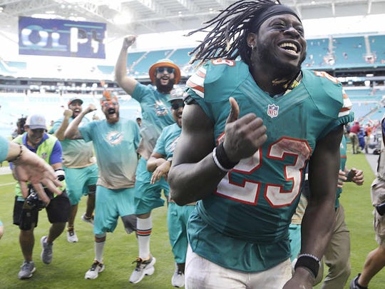 Miami running back Jay Ajayi is congratulated by fans as he leaves the field, at the end of the Dolphins' 28-25 victory against the Buffalo Bills on Sunday in Miami Gardens, Fla. Ajayi tied an NFL record by surpassing 200 yards rushing for the second game in a row.