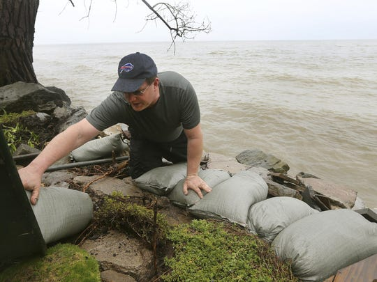 Rob Bauman arranges sandbags along the banks of Lake Ontario on property that belongs to his parents on Edgemere Drive, Tuesday in Greece, New York.