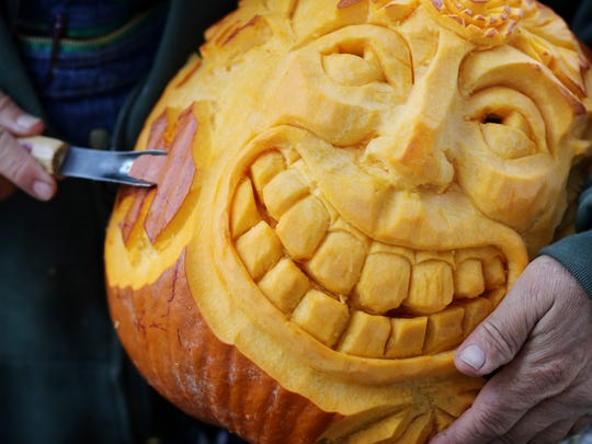 A face is carved into a pumpkin by a member of the Leipers Fork Carving Club at Franklin's Pumpkin Fest held Saturday October 28, 2017.