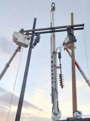A crew from the Otero County Electric Cooperative works on repairs after the storm.