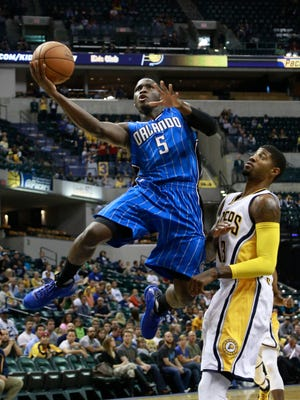 Orlando Magic guard Victor Oladipo (5) shoots while defended by Indiana Pacers forward Paul George in the first half of an NBA preseason basketball game, Thursday, Oct. 8, 2015, in Indianapolis. (AP Photo/R Brent Smith)