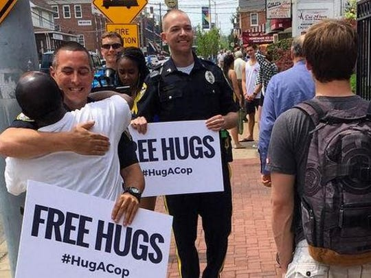 Newark police Officer Aaron Olicker, left, and  Cpl. James Spadola take part in the Hug a Cop effort on Main Street. Spadola is running for a seat in the Delaware General Assembly.