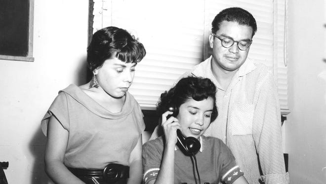 Undated photo of two women and a man in an office.