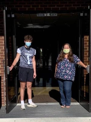 Coosa Christian sophomore Thomas Skaggs and K4 teacher Nicole McCauslin open the doors at the school. The doors will open Aug. 18 for students to return to campus.