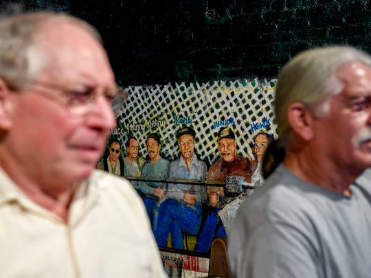 "Robert ""Hawk"" Miller, left, and Jerry Crouch, right, sit at stools while posing for a portrait next to a mural depicting them and other regulars at Jack's Pool Room in Paris, Tenn., Wednesday, July 25, 2018."