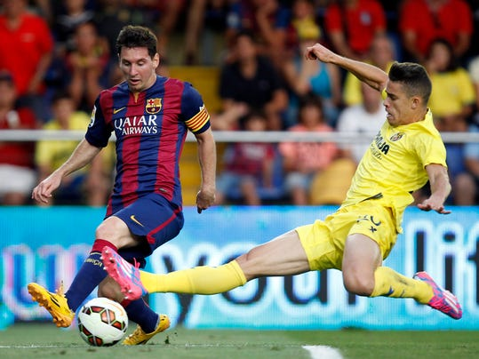Barcelona's Lionel Messi, from Argentina, challenges for the ball with Villarreal's Grabiel Paulista from Brazil  during a Spanish La Liga soccer match at the Madrigal stadium in Villarreal, Spain, on Sunday, Aug 31, 2014.(AP Photo/Alberto Saiz)
