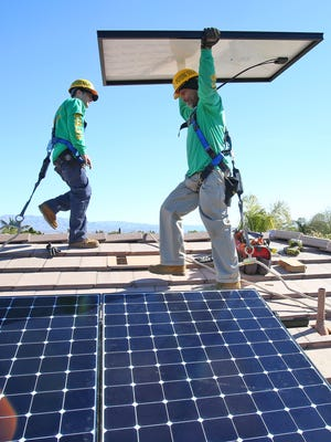 Potere Solar technicians Benny Lopez, right, and Anthony Cataudella install panels at a Rancho Mirage home on Jan. 26, 2016.
