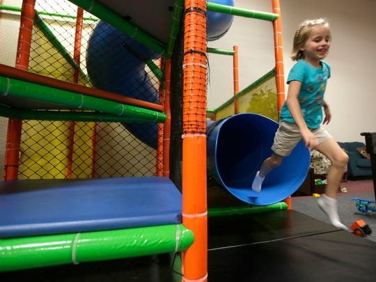 Gwen Rezin, 6, leaps out of a slide in the Blu Play