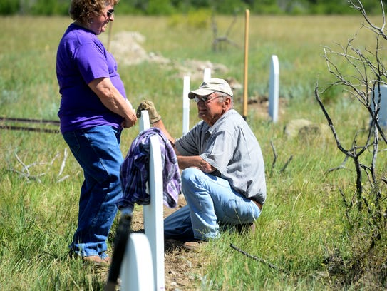 Jim Parker kneels at newly planted grave marker in