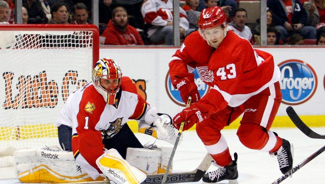 Detroit Red Wings center Darren Helm (43) tries to control the puck in front of Florida Panthers goalie Roberto Luongo during the third period at Joe Louis Arena.