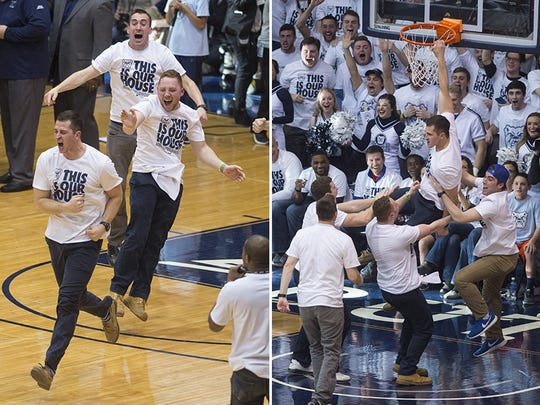 Nick Waltz celebrates and hangs on the rim after hitting a half-court shot to win a year's worth of Penn Station sandwiches.
