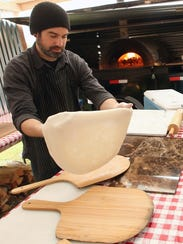 Scott Williams stretches out some dough for pizza.